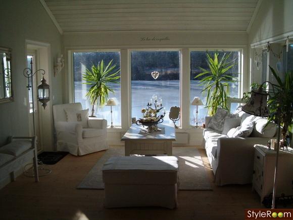 vardagsrum,högt i tak,stora fönster,pall,blommor,lykta,vit fåtölj,vit soffa